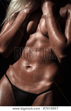 muscular female abdominal tension against black background
