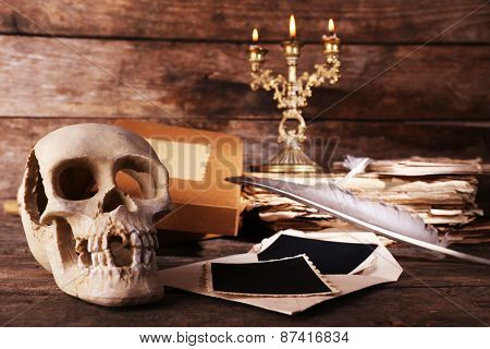 Still life with human skull, retro book and quill on wooden background