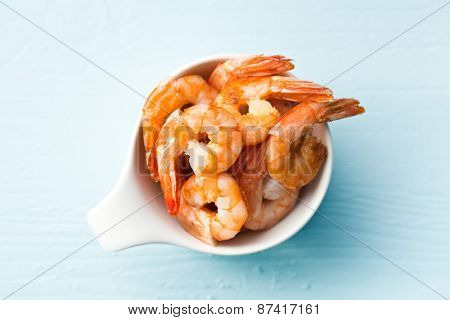 grilled prawns in a bowl on blue table