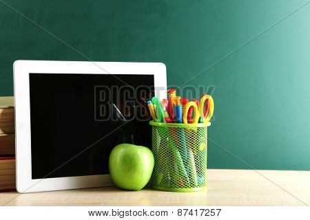 Digital tablet, books, colorful pens and apple on desk in front of blackboard