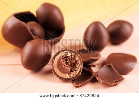Chocolate Easter eggs on wooden table with tulle, closeup