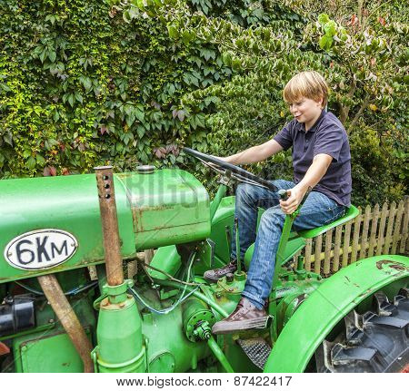 Boy Playing With An Old Tractor