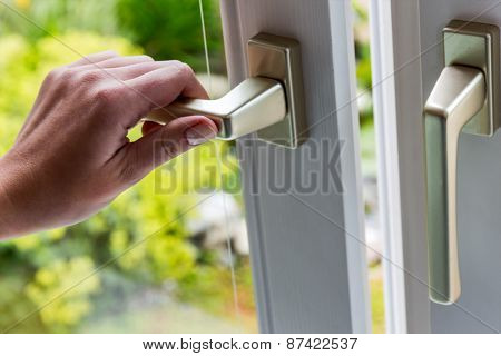 a woman opens a window to air the apartment. fresh air in the room