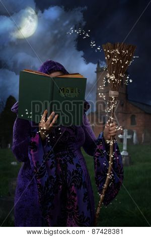 Woman wearing purple cloak in graveyard with book of magic spells and broomstick