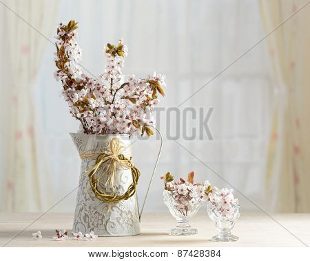 Springtime blossom in vase and antique glasses