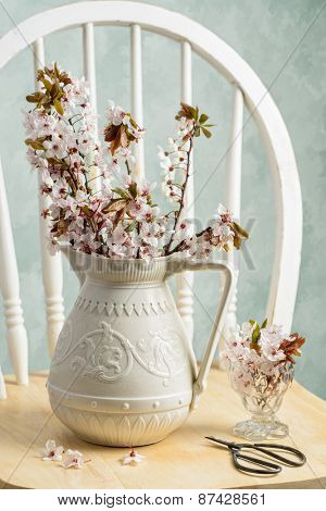 Spring blossom in antique pottery vase with scissors on rustic chair