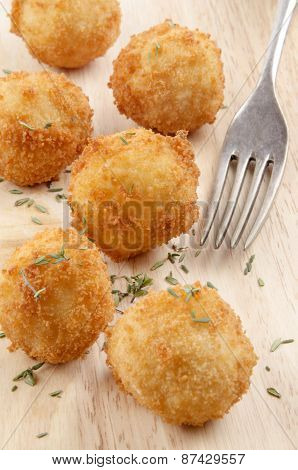Fried Potato Pops On Wood With Fork