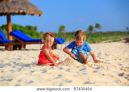 kids playing with sand on summer beach