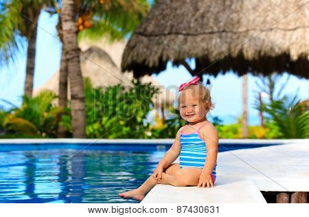 cute toddler girl playing in swimming pool at summer beach