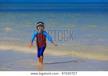 little boy playing with water on summer beach