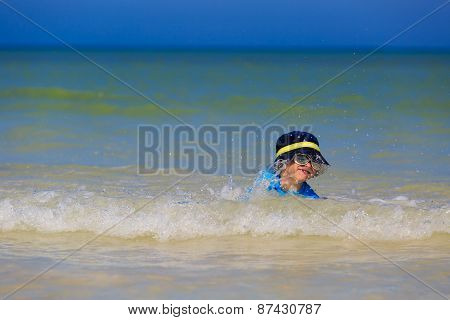 little boy playing with waves on the beach