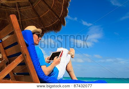 man with touch pad on the beach