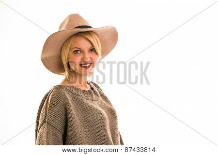 Woman In A Sweater And Cowboy Hat Smiling On A White Background