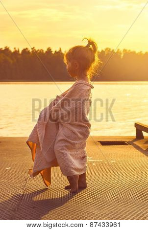 Toned portrait of Cute little kid watching at the sea at sunset