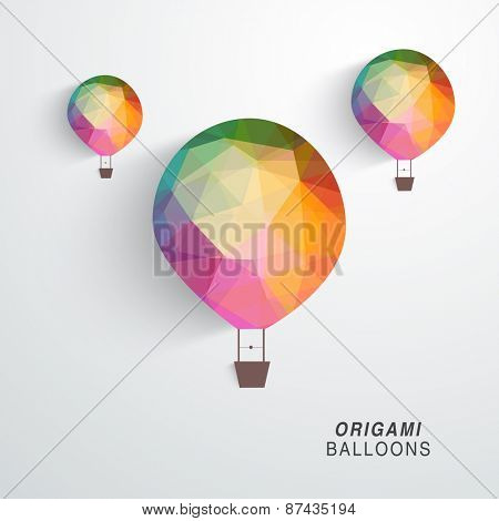 Colorful origami hot air balloon flying on grey background.