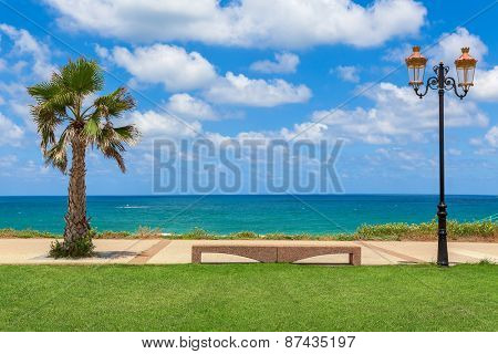 Stone bench between palm and decorative lamppost with beautiful view on Mediterranean sea under blue sky with white clouds in Israel.