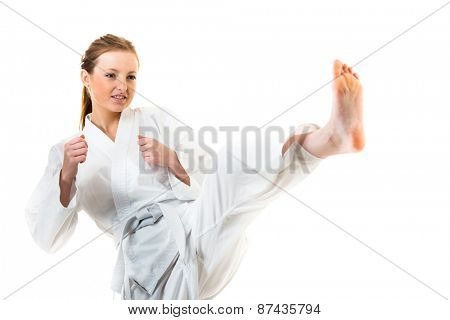 Beautiful caucasian, young, woman makes a kick in karate kimono on white background