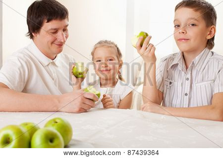Father and children eating apples. Family at home in the kitchen