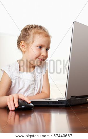 Child with laptop indoors. Happy little girl playing computer at home.
