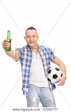 Vertical shot of a young football fan holding a beer, cheering and looking at the camera isolated on white background
