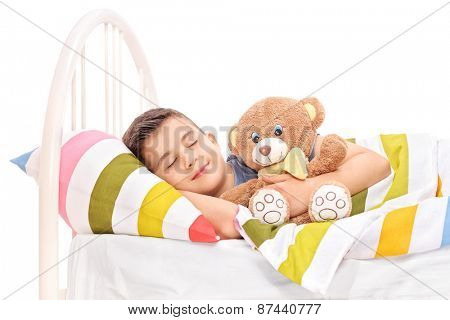Cute little kid sleeping with a teddy bear covered with a blanket in bed isolated on white background