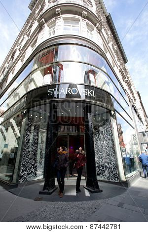 VIENNA, AUSTRIA - APRIL 6, 2015: Shoppers exit a Swarovski crystal retail store. Swarovski AG is an Austrian producer of luxury cut lead glass.