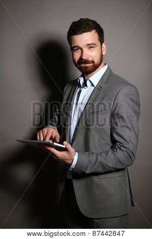 Businessman with a tablet computer. business man using digital tablet computer, leaning against a bl
