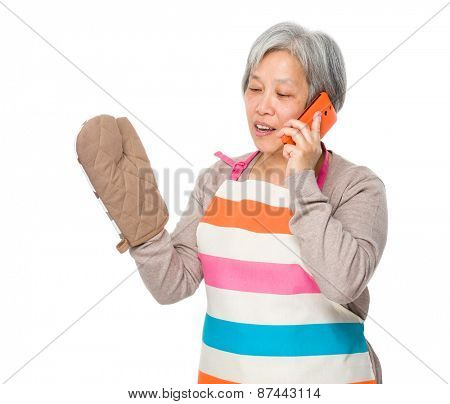Busy old lady with kitchen apron and talk to mobile phone