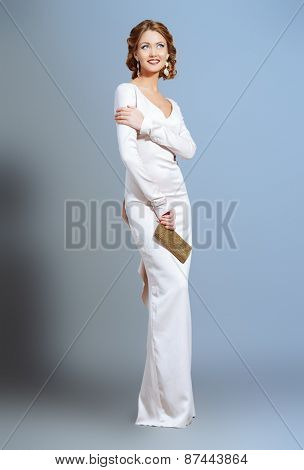 Full length portrait of a beautiful woman in elegant evening dress posing over gray background. Fashion shot. Hairstyle.