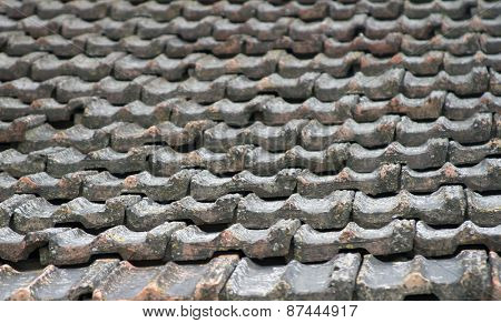 The roof of an old house covered with gray tiles.