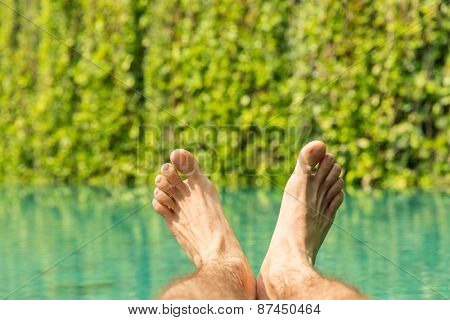 leisure, people, travel and tourism concept - close up of male feet over resort swimming pool