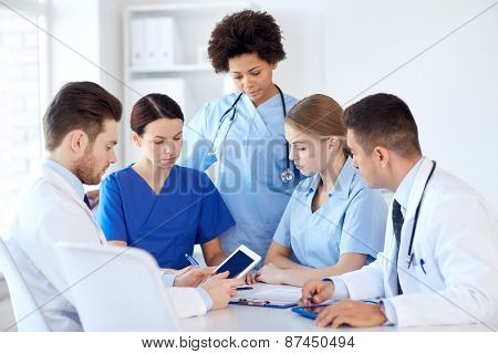 hospital, profession, people and medicine concept - group of doctors with tablet pc computers meeting at medical office