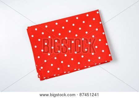 red and white dotted place mat on white background