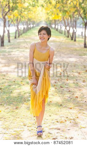 Portrait Of Young Beautiful Asian Woman Wearing Yellow Dress Relaxing And Happy Emotion In Flowers B