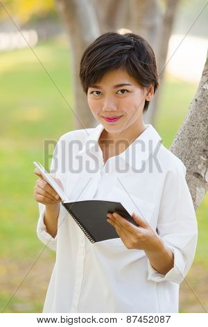 Portrait Of Young Beautiful Woman Wearing White Shirt Standing In Park With Book In Hand Looking To