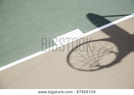 Abstract Shadow of Basketball Hoop and Net Against Court Surface.
