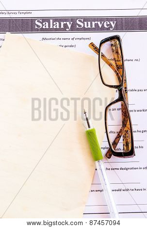 Glasses And Pen On Salary Survey From
