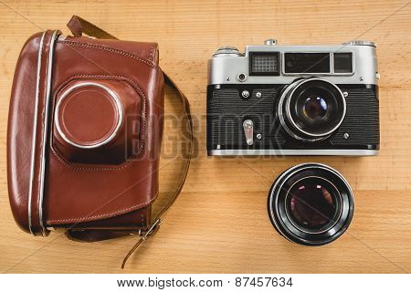 Retro Photography Set Of Camera, Case And Lens On Wooden Background