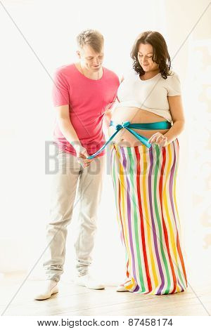 Toned Shot Of Husband Untying Bow On Pregnant Wife Abdomen
