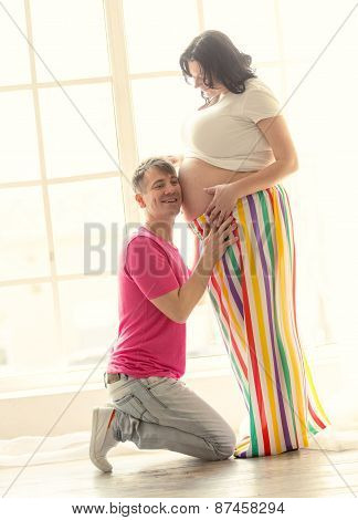 Handsome Man Kneeling And Listening To The Belly Of Pregnant Wife