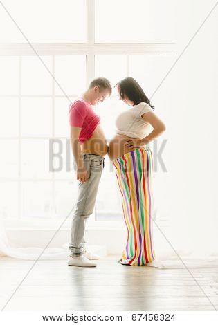 Toned Shot Of Happy Young Pregnant Couple Touching By Stomachs