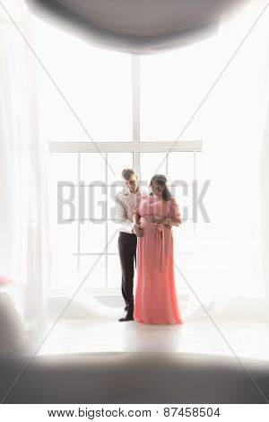 Silhouette Photo Of Pregnant Couple Embracing Against Big Window