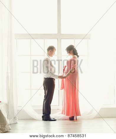 Toned Photo Of Beautiful Pregnant Couple Holding Hands At Window