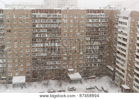 Snowfall On Residential Building Facade Background. Winter Mood