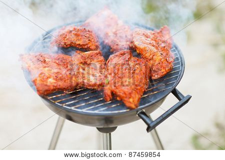 food, eating, cooking and summer holidays concept - close up of meat on barbecue grill outdoors