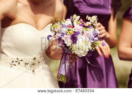 Bride holding flower bouquet with bride's maids