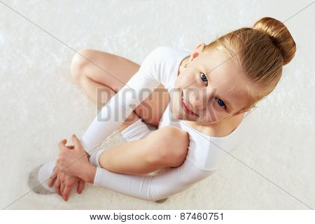 Children Sport. Little Sporty Girl Sitting On The White Carpet.