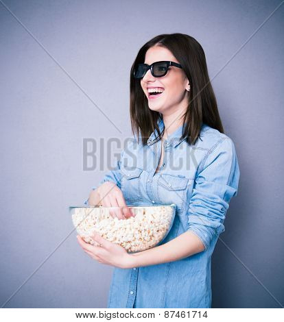 Laughing woman in cinema glasses holding bowl with popcorn over gray background and looking away