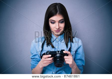 Surprised young woman looking on camera screen over gray background