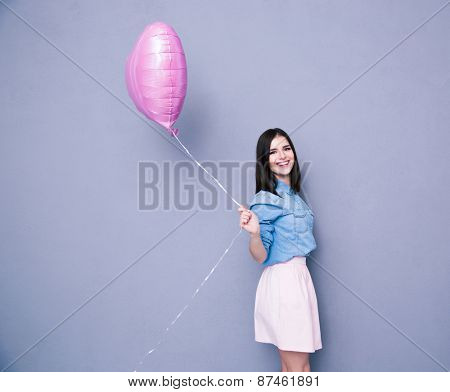 Cheerful woman holding balloon and looking at camera over gray background. Wearing in shirt and skirt
